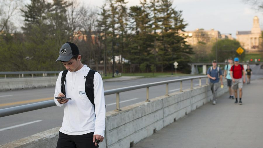 A student checks his phone while passing over the Iowa Avenue bridge on Wednesday, April 19, 2017. The bridge was built in 1916, after replacing the Centennial Bridge, it was later updated in 1985. (The Daily Iowan/Joseph Cress)