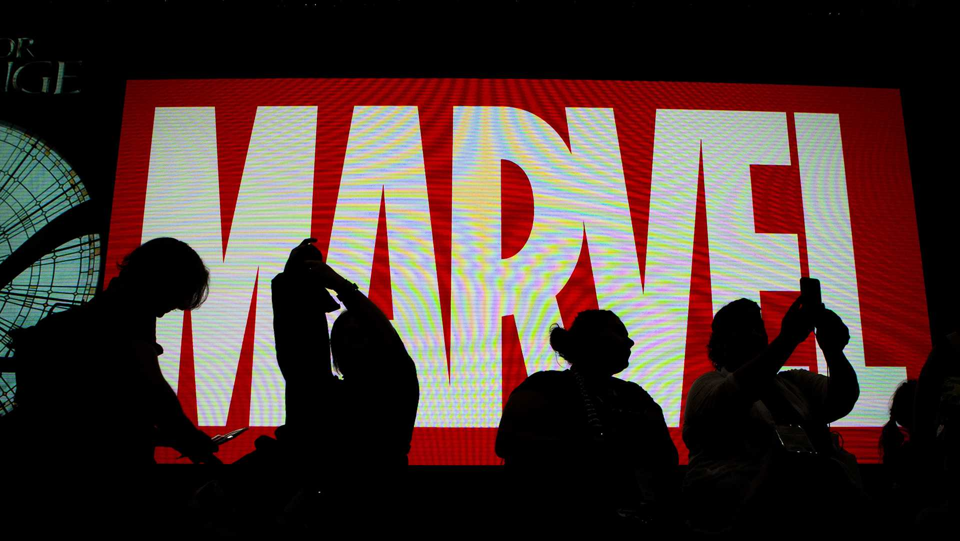 Attendees sit in front of an illuminated Marvel sign during the second day of Comic-Con 2016 on July 21, 2016 in San Diego. (Harrison Hill/Los Angeles Times/TNS)