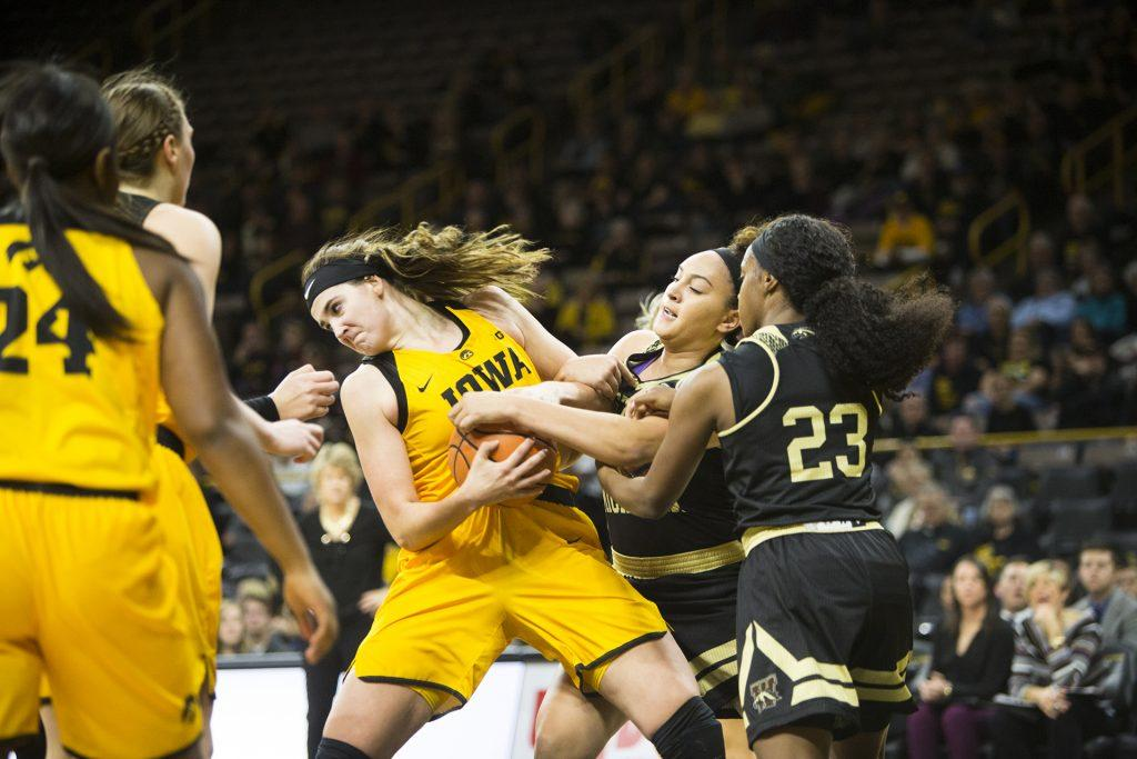Iowa center Megan Gustafson fights for an offensive rebound away from Western Michigan defenders during the Iowa/Western Michigan womens basketball game in Carver-Hawkeye Arena on Sunday, Nov. 19, 2017. The Hawkeyes defeated the Broncos, 79-56. (Joseph Cress/The Daily Iowan)