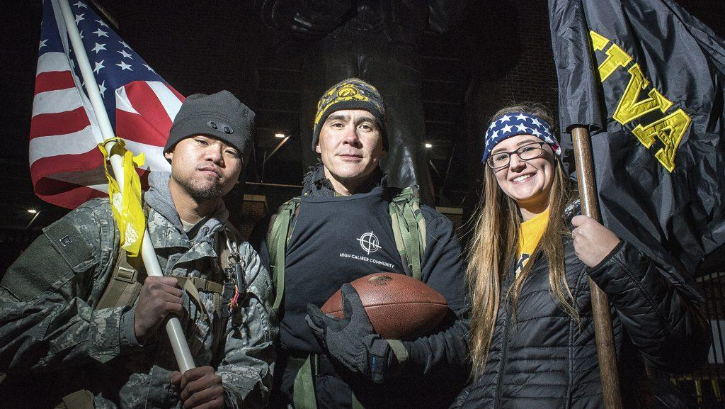 Ruck March volunteers Private Chris Phoumy (left), Ret. Major Kent Christen (center), and Private Courtney Packard (right) pose for a group portrait shortly before starting their 22-mile march on Wednesday. The event's goal is to march the Iowa/Nebraska game ball from stadium to stadium to raise awareness of the veteran/suicide issue. According to the VA estimates, there are 22 suicides a day among current and former service members. (James Year/The Daily Iowan)