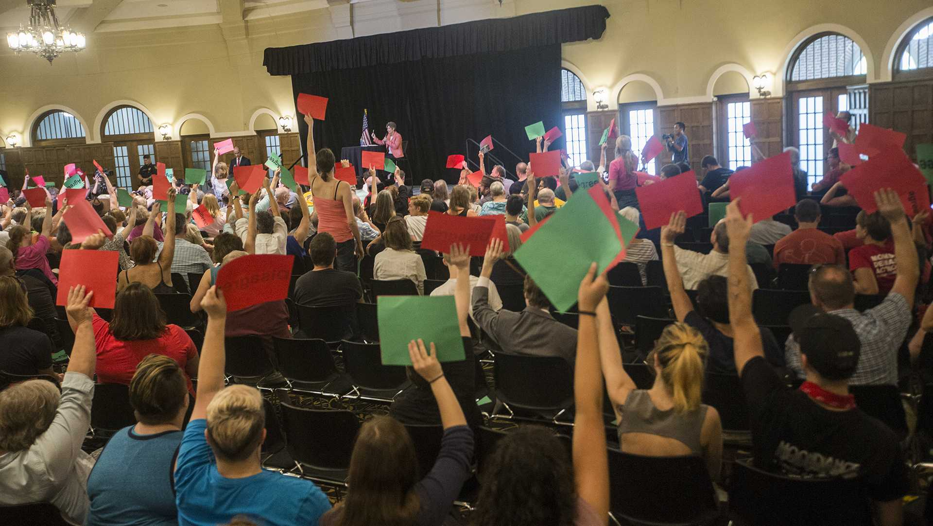 Crowd members hold signs in disapproval during a town hall meeting in the IMU on Friday, Sept. 22, 2017. While Sen. Ernst spoke in the IMU a protest was held outside in Hubbard park. (Joseph Cress/The Daily Iowan)