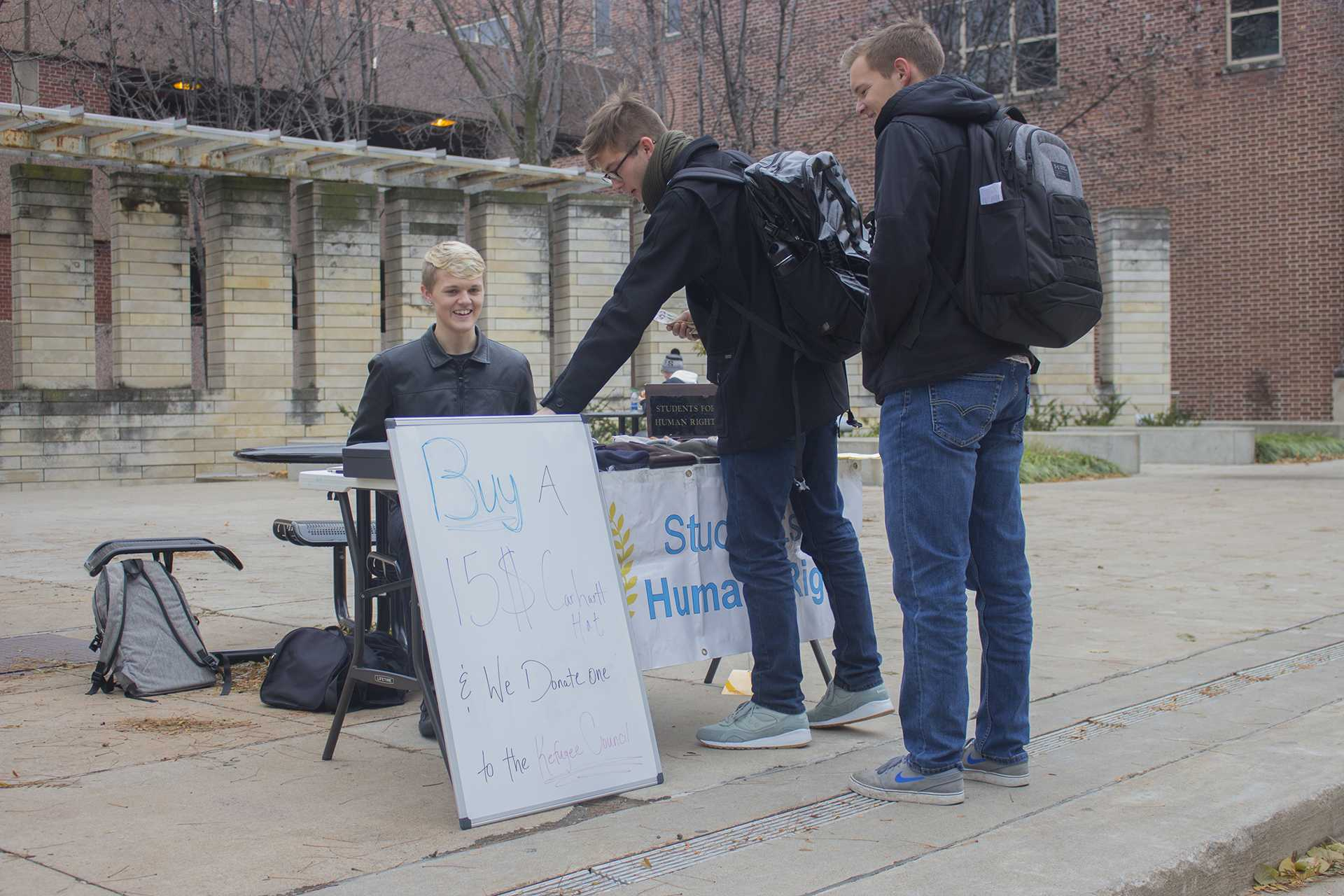 UI sophomore and Students for Human Rights representitive Jon Seedorff sells Carhartt hats on the T. Anne Cleary Walkway on Monday, Nov. 13, 2017. Students for Human Rights is also hosting an All You Can Eat Pancake Palooza on Thursday, Nov. 16 from 5 p.m. to 9 p.m. at Old Brick Church, with all the proceeds from both fundraisers doing to the Refugee Council USA to support refugees both domestically and abroad. (Lily Smith/The Daily Iowan)