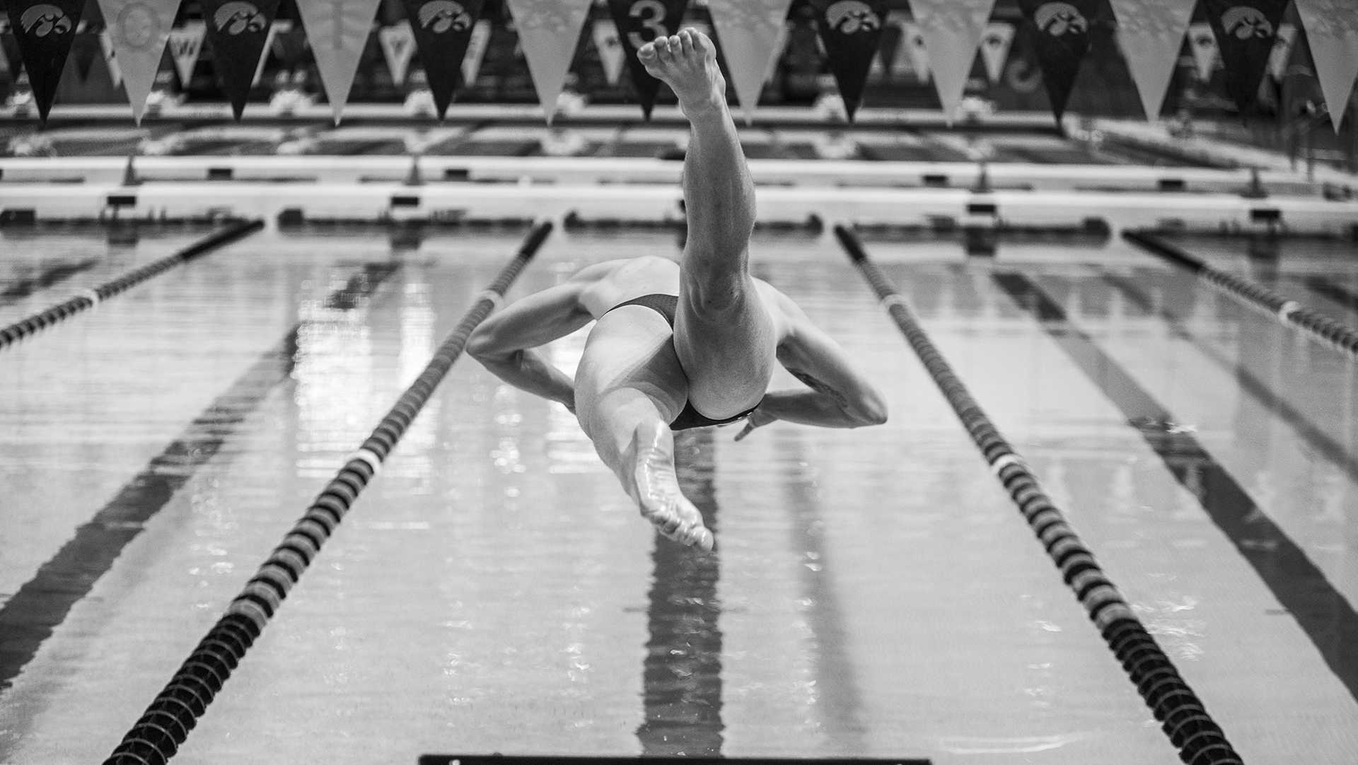 A member of the Iowa men's 400m relay team leaves the blocks during the Senior Day meet between Iowa and Minnesota at the Campus Recreation and Wellness Center on Friday, Oct. 27, 2017. The Iowa men's swimming team beat the 21st ranked Minnesota Golden Gophers, 168-132. (Ben Smith/The Daily Iowan)