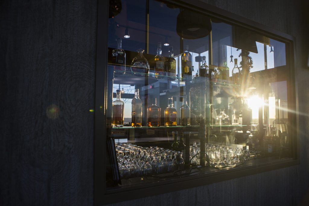 Sun shines through glasses in a bar during a ribbon cutting event for the Hilton Garden Inn on Clinton Street on Thursday, Nov., 30, 2017. The 12th floor of the hotel features a rooftop bar and restaurant that is open to the public. The hotel opened in October. (Joseph Cress/The Daily Iowan)