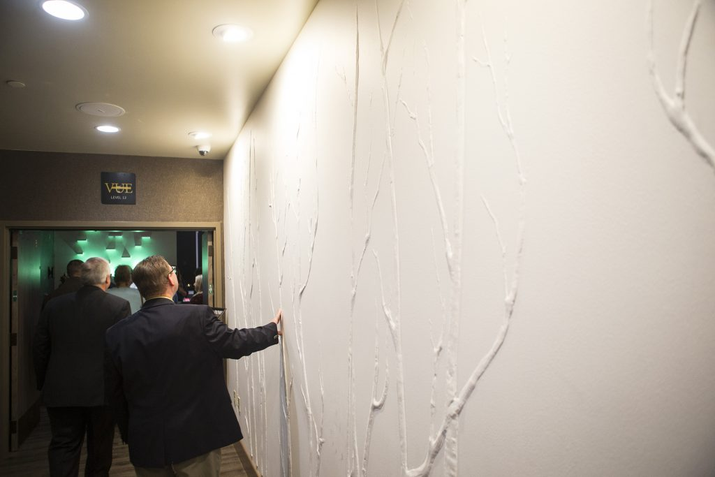 Guests feel a textured wall on the 12th floor during a ribbon cutting event for the Hilton Garden Inn on Clinton Street on Thursday, Nov., 30, 2017. The 12th floor of the hotel features a rooftop bar and restaurant that is open to the public. The hotel opened in October. (Joseph Cress/The Daily Iowan)