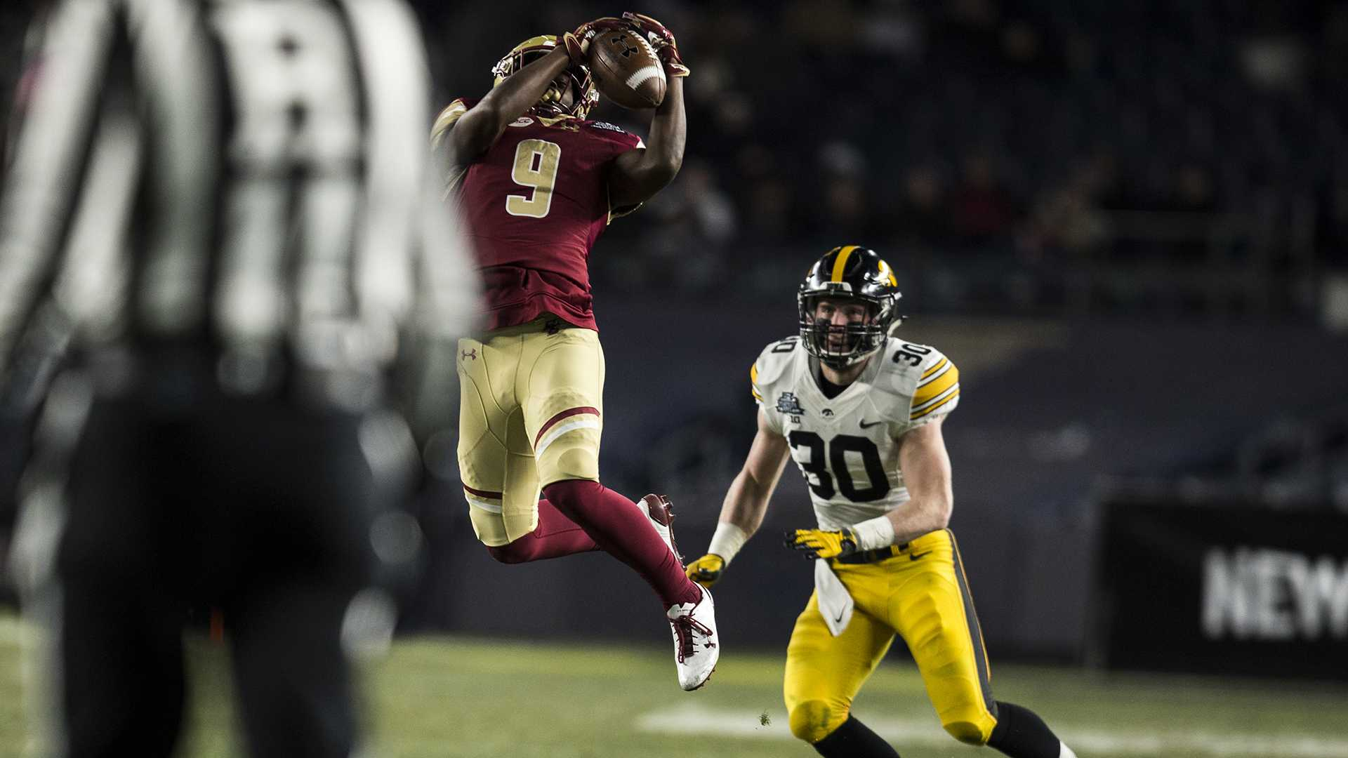 Boston College wide receiver Kobay White (9) catches the ball over Iowa's Jake Gervase (30) during the first half of the New Era Pinstripe Bowl at Yankee Stadium in New York on Wednesday, Dec. 27. The score going into the second half is 17-10. (Ben Allan Smith/The Daily Iowan)