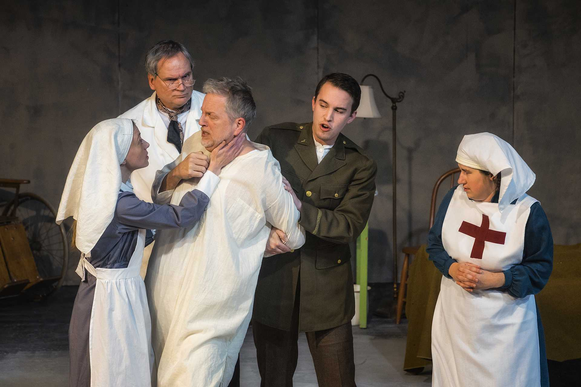 Actors, as medical professionals, help calm a shell-shocked patient during a dress rehearsal for the play Shell Shocked on Wednesday, Dec. 13, 2017. The performance centers on a doctor's search to understand and improve conditions on the Western Front during World War 1. (James Year/The Daily Iowan)