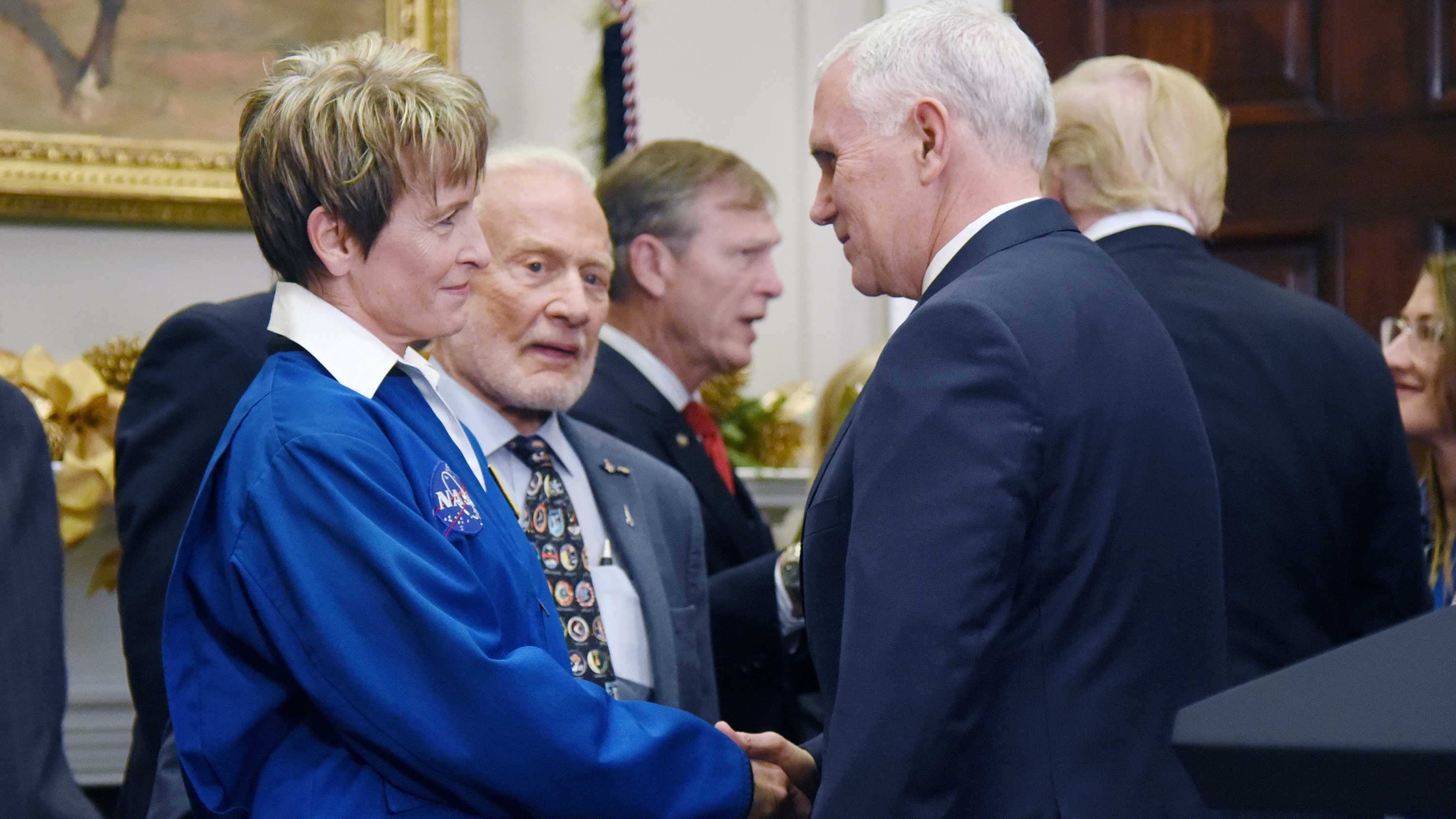U.S. Vice President Mike Pence shakes hands with NASA astronaut Peggy Whitson, left, as former astronaut Buzz Aldrin looks on after a signing ceremony reinstating the National Space Council with the goal of sending American astronauts back to deep space during an event on Monday, Dec. 11, 2017 in the Roosevelt Room of the White House in Washington, D.C. (Olivier Douliery/Abaca Press/TNS)
