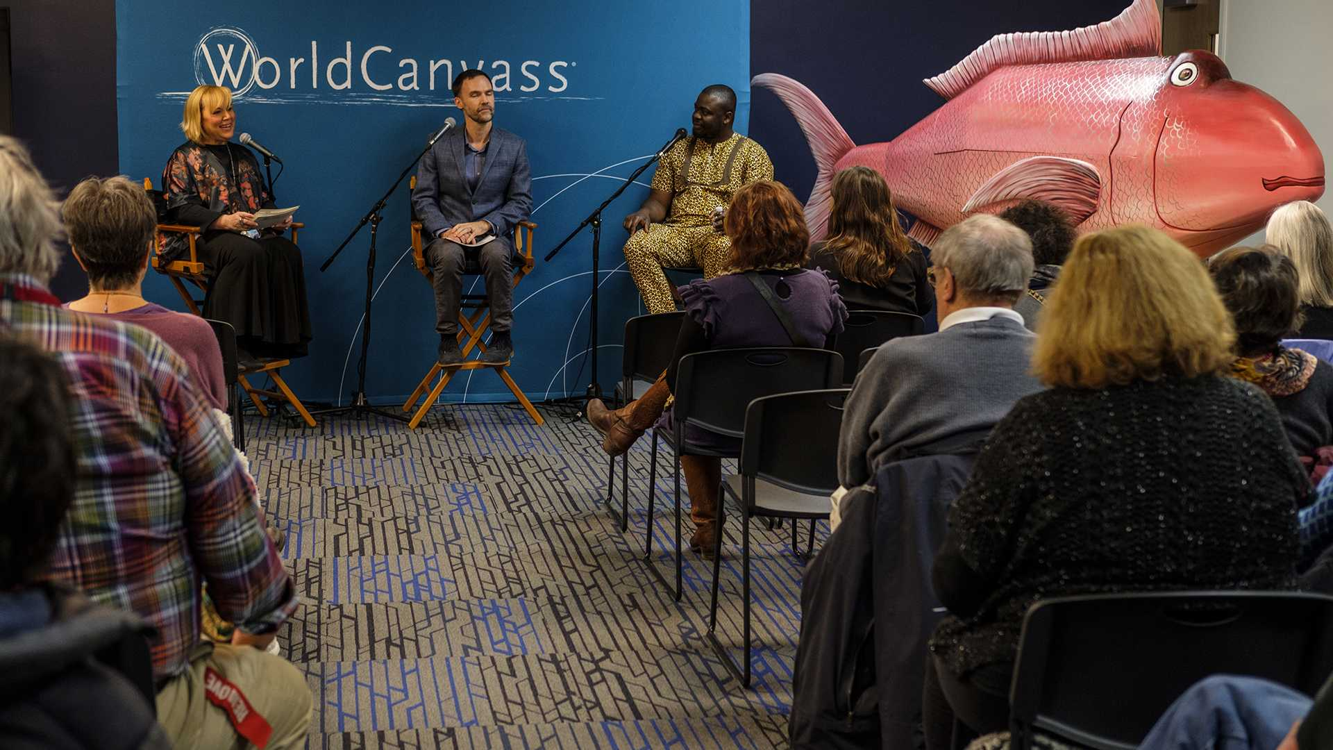 Host Joan Kjaer, Cory Gundlach, and UI Museum of Art artist-in-residence Eric Adjetey Anang speak at a World Canvass event at Merge in Iowa City on Thursday, Dec. 7, 2017. The night's event focused on art and the afterlife and featured a large fish shaped coffin made by Anang. (Nick Rohlman/The Daily Iowan)