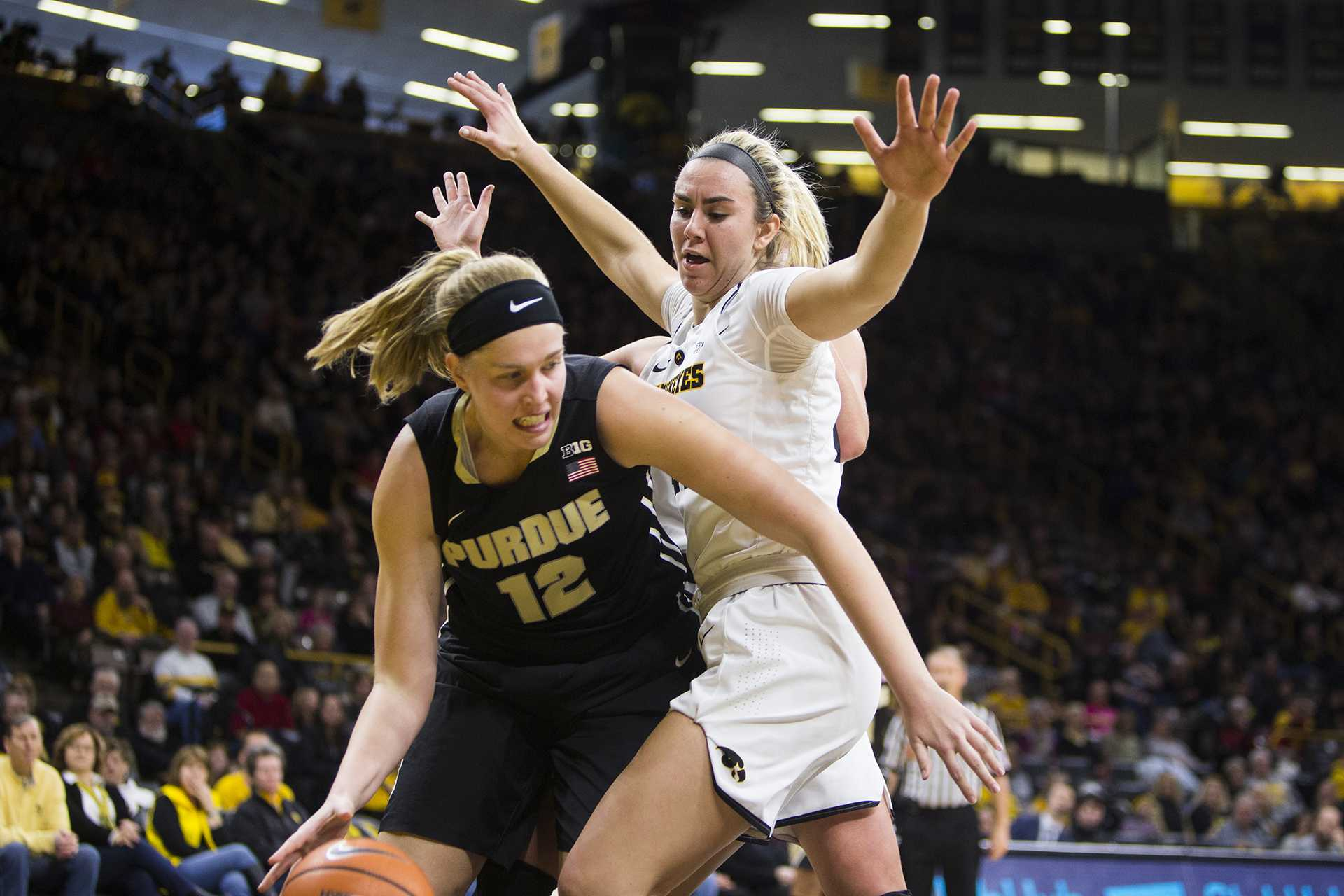 Purdue center Nora Kiesler dribbles past Iowa forward Hannah Stewart during an Iowa/Purdue women's basketball game in Carver-Hawkeye Arena on Saturday, Jan. 13, 2018. The Boilermakers defeated the Hawkeyes, 76-70. (Joseph Cress/The Daily Iowan)