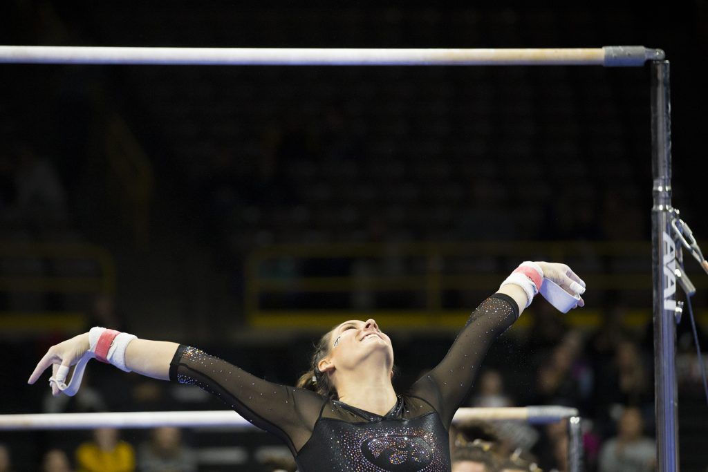 Iowa's Lanie Snyder dismounts the uneven bars during the Iowa/Ohio State gymnastics meet in Carver-Hawkeye Arena on Friday, Jan. 19, 2018. The GymHawks defeated the Buckeyes, 195.725 to 195.300, to win their home opener. (Lily Smith/The Daily Iowan)
