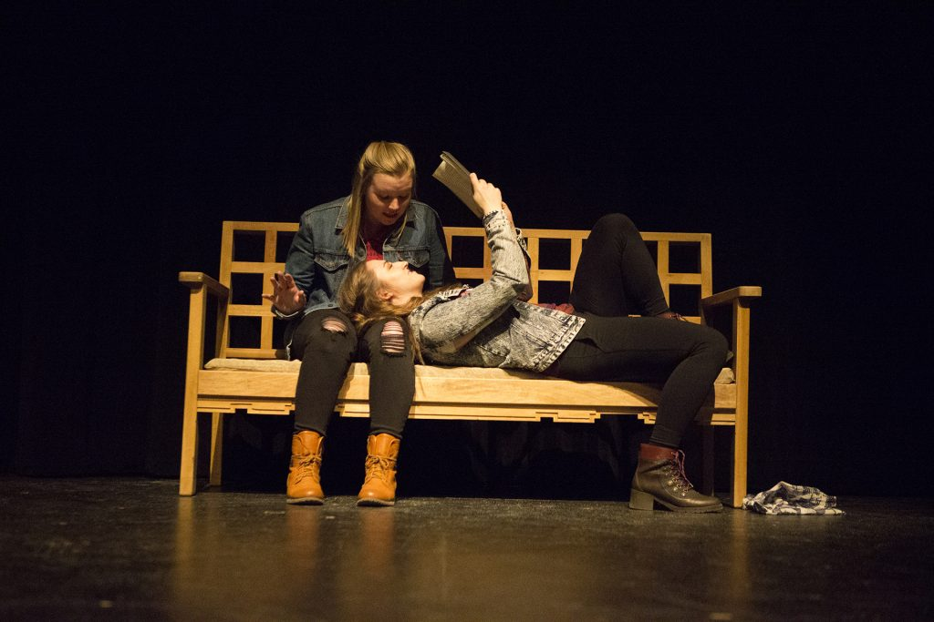 Junior+Kaylyn+Kluck%2C+playing+Sarai%2C+reads+a+book+as+her+girlfriend+Iris%2C+played+by+sophomore+Emilia+Bendler+watches+during+a+dress+rehearsal+of+Western+Tinder.+This+student+written+and+directed+play+examines+homosexuality+and+intolerance+in+small+town+Wyoming.+%28Katie+Goodale%2FThe+Daily+Iowan%29