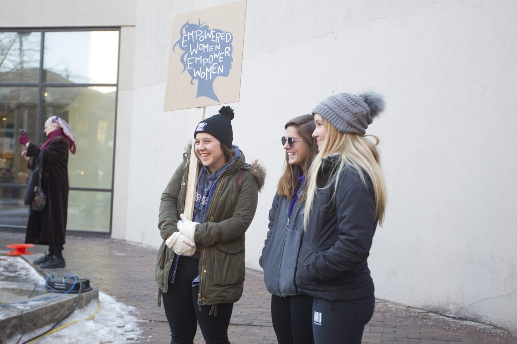 Students smile during the Women's March on January 20, 2018. Hundreds gathered on the Ped Mall to listen to speakers and march for women's rights. (Katie Goodale/The Daily Iowan)