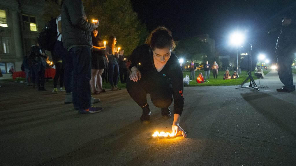 UI+sophomore+Chloe+Stone+sets+a+candle+down+during+the+UI+Sister+Vigil+for+Survivors+of+Campus+Sexual+Assault+on+the+Pentacrest+on+Tuesday%2C+Oct.+17%2C+2017.+The+event+included+letter+writing+to+Iowa+senators+and+the+signing+of+thank+you+state+of+Iowa+flags+to+senators+fighting+the+withdrawal+of+Title+IX+protections+for+survivors+of+sexual+assault.+%28Lily+Smith%2FThe+Daily+Iowan%29