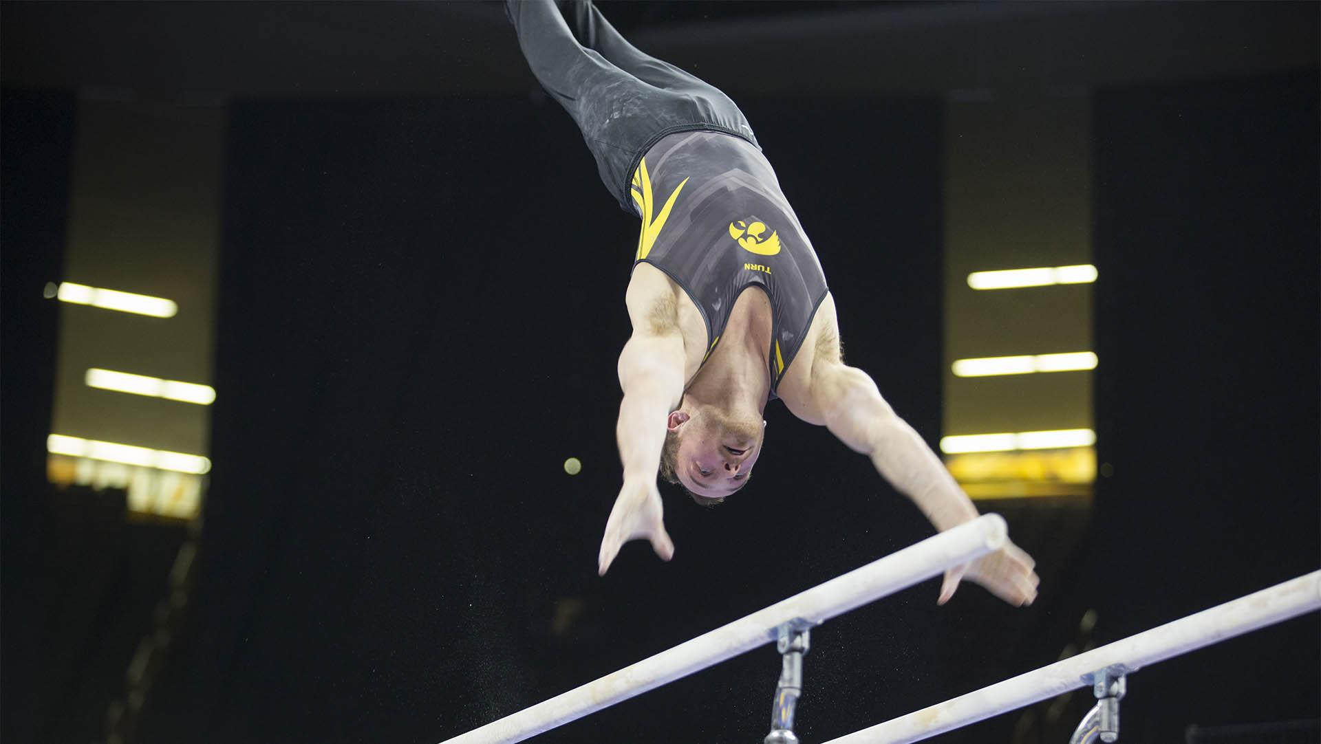 Dylan Ellsworth competes on the parallel bars during men's gymnastics on Feb. 23, 2018. Ellsworth 13.750 for his performance on the parallel bars. The Cornhusters defeated the Hawkeyes 402.8 to 398.5. (Katie Goodale/ The Daily Iowan)