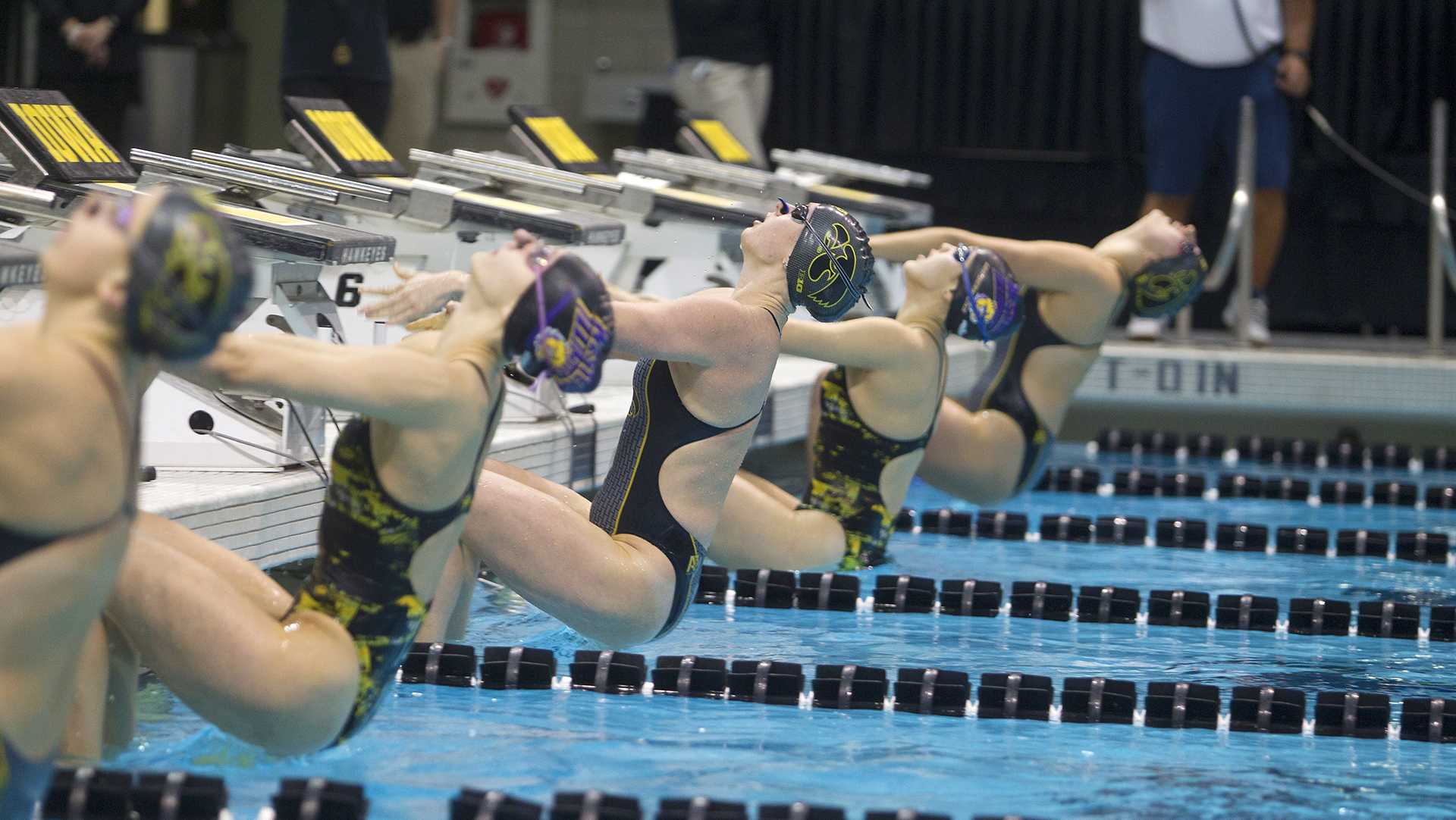 Swimmers dive into the pool for the Women's 50-yard backstroke during a meet between University of Iowa and Western Illinois on Friday, Feb. 2, 2018 at the University Aquatic Center.
