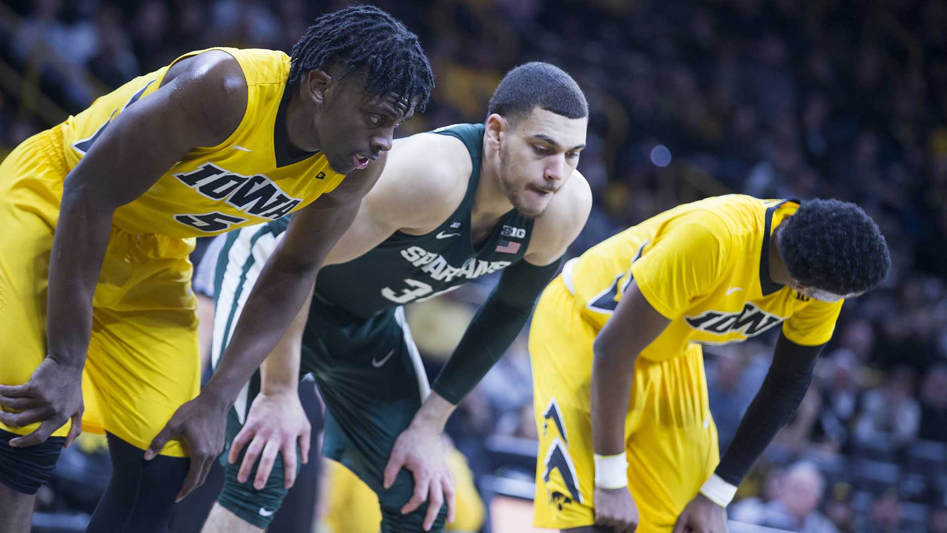Iowa's Tyler Cook, Michigan State's Gavin Schilling, and Iowa's Isaiah Moss line up for a free throw attempt during a basketball game between Iowa and Michigan State on Tuesday, Feb. 6, 2018. The Spartans defeated the Hawkeyes 96-93. (Shivansh Ahuja/The Daily Iowan)