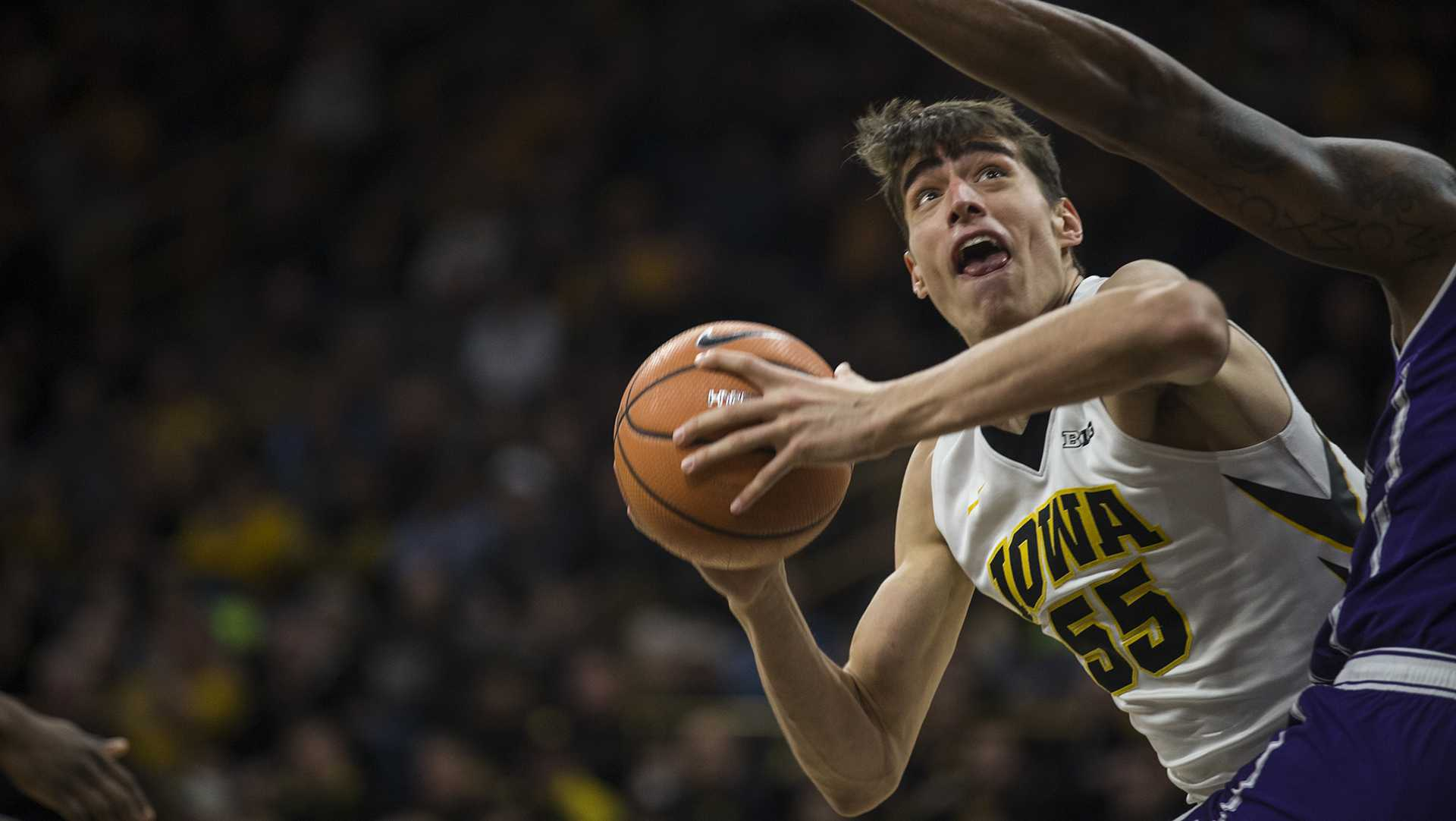 Iowa forward Luka Garza (55) looks for an open shot against a Northwester defender during the Senior Day men's basketball game between Iowa and Northwestern at Carver-Hawkeye Arena on Sunday, Feb. 25, 2018. The Hawkeyes defeated the Wildcats 77-70. (Ben Allan Smith/The Daily Iowan)
