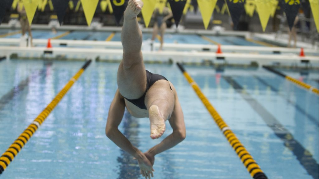 Weston Credit of Iowa diver into the pool during the Men's 500 yard freestyle at a swim meet between University of Iowa and Western Illinois on Friday, Feb. 2, 2018 at the University Aquatic Center. Swimmers competed in a variety of events including relays and freestyle swimming. (Katie Goodale/The Daily Iowan)
