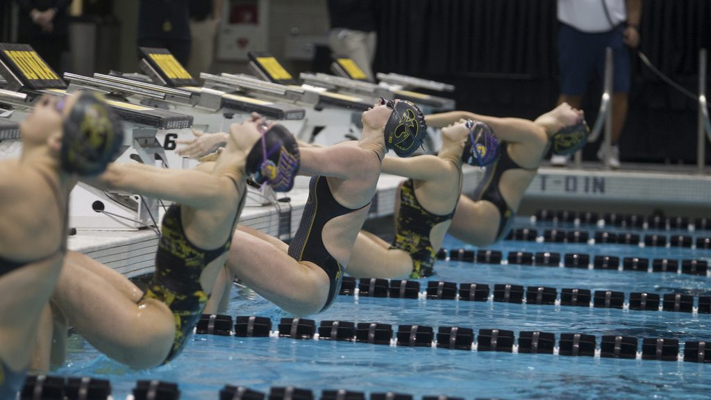 Swimmers dive into the pool for the Womens 50 yard backstroke during a swim meet between University of Iowa and Western Illinois on Friday, Feb. 2, 2018 at the University Aquatic Center. Swimmers competed in a variety of events including relays and freestyle swimming. (Katie Goodale/The Daily Iowan)