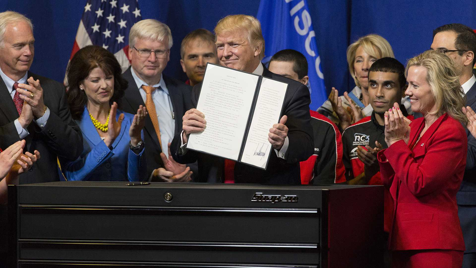 """President Donald Trump signs the so-called """"Buy American, Hire American"""" executive order on April 18, 2017, during a visit to Snap-on Inc. in Kenosha, Wis. The orders clamp down on guest worker visas and require federal agencies to buy more goods and services from U.S. companies and workers. (Mark Hoffman/Milwaukee Journal Sentinel/TNS)"""