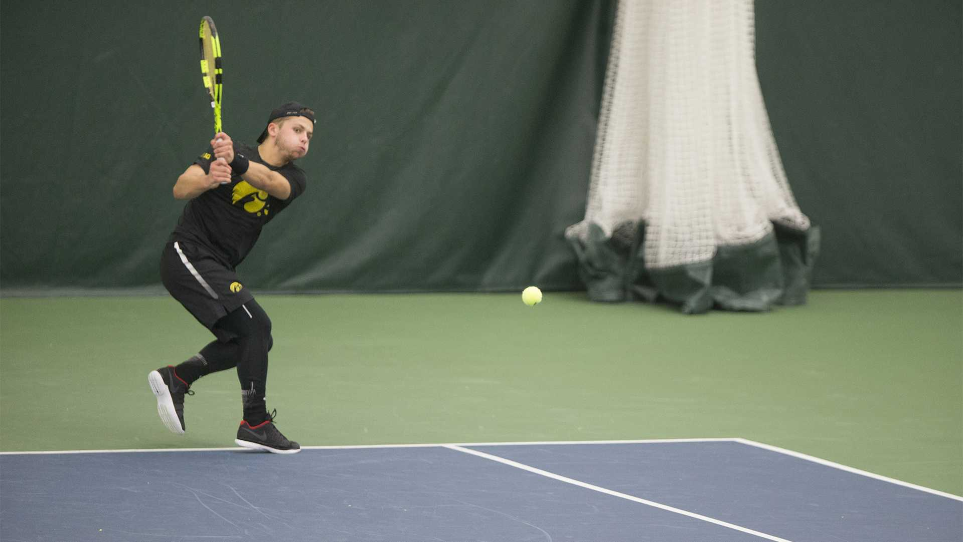 Iowa's Will Davies wails a backhand during a tennis match between Iowa and Western Michigan in Iowa City on Friday, Jan. 19, 2018. The Hawkeyes earned the doubles point but lost the match overall, 5-2. (Shivansh Ahuja/The Daily Iowan)