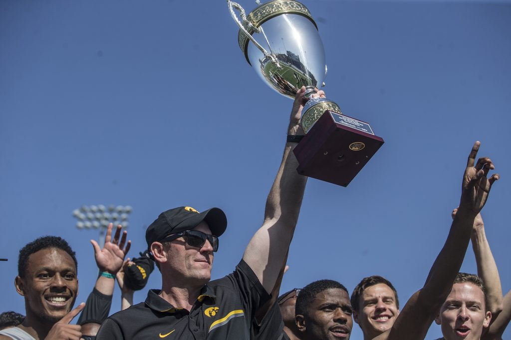 Iowa head coach Joey Woody holds the trophy for first place after the 2018 Drake Relays at Drake Stadium in Des Moines, Iowa on Saturday, April 28, 2018. Iowa placed first in the meet.
