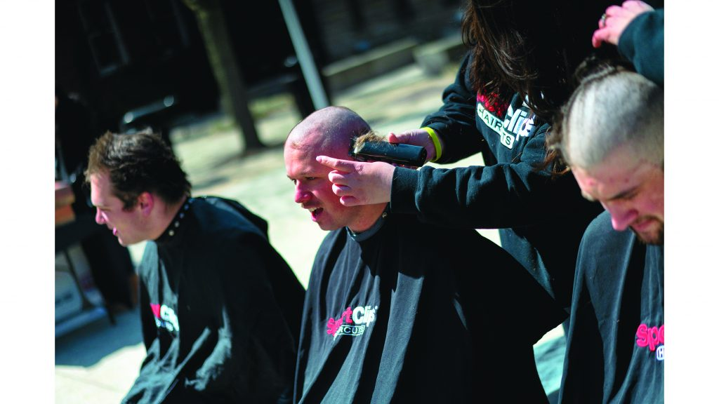 UI+students+have+their+heads+shaved+on+the+T.+Anne+Cleary+Walkway+on+Wednesday%2C+April+4%2C+2018.+Be+the+Match+has+asked+students%2C+faculty%2C+and+alumni+to+shave+their+heads+in+support+of+cancer+patients.+%28Lucas+Xu%2FThe+Daily+Iowan%29