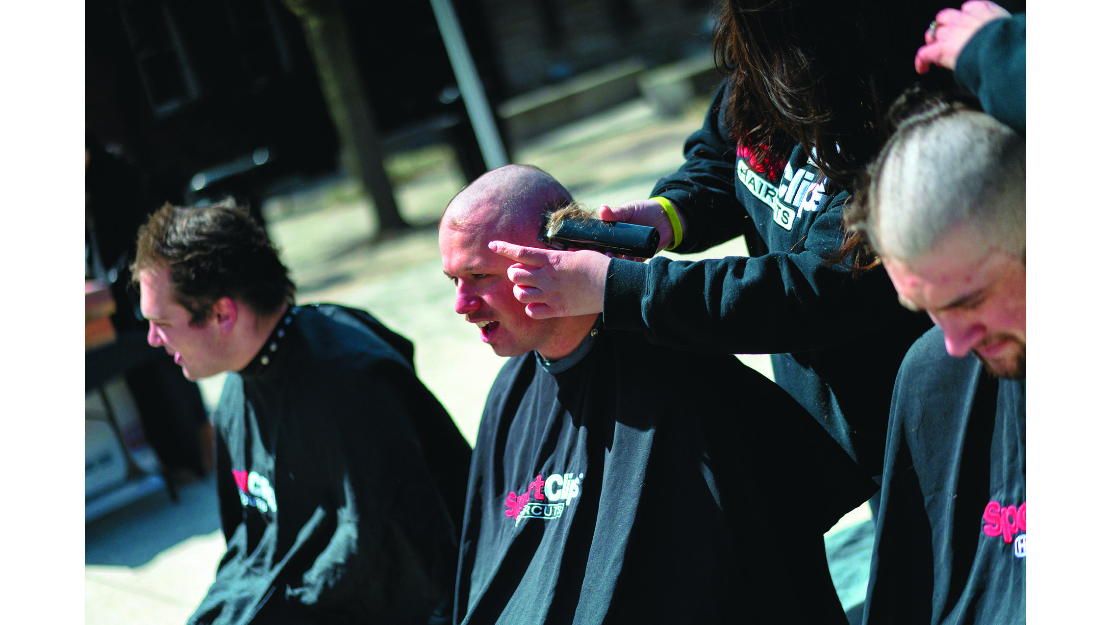 UI students have their heads shaved on the T. Anne Cleary Walkway on Wednesday, April 4, 2018. Be the Match has asked students, faculty, and alumni to shave their heads in support of cancer patients. (Lucas Xu/The Daily Iowan)