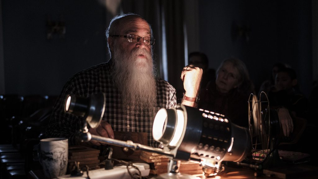 Historian+Mike+Zahs+demonstrates+a+magic+lantern+in+the+Old+Capitol+Senate+Chamber+on+Dec.+9.+Zahs+projected+slides+as+part+of+a+magic-lantern+demonstration+meant+to+introduce+people+to+an+early+from+of+visual+communication.+%28Nick+Rohlman%2FThe+Daily+Iowan%29