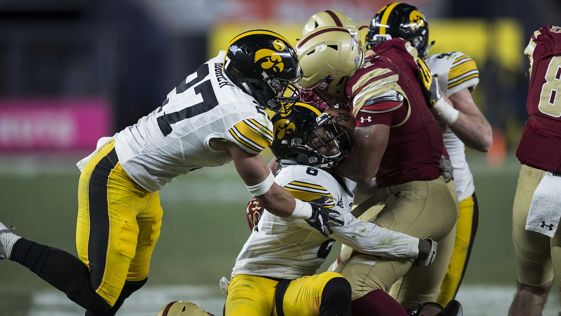 Iowa's Amani Hooker (27) and Matt Hankins (8) sack Boston College quarter back Darius Wade (4) during the New Era Pinstripe Bowl at Yankee Stadium in New York on Wednesday, Dec. 27. The Hawkeyes went on to win 27-20.