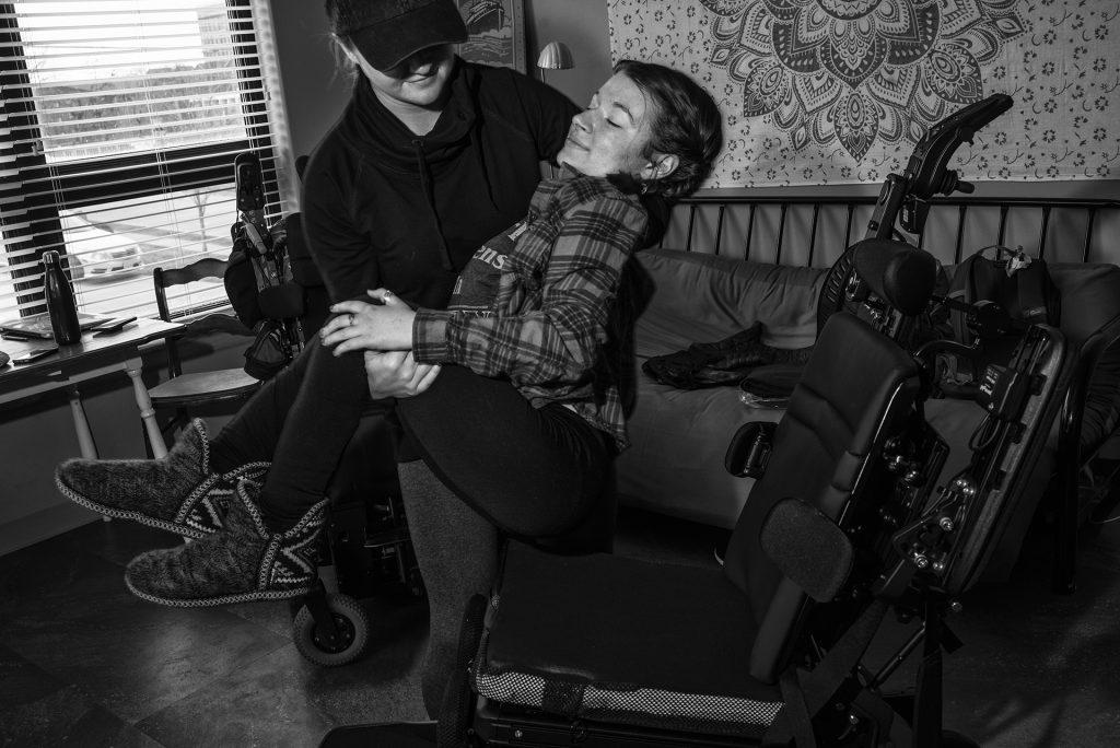 Hannahs longtime friend Maddy Tornabane helps her into a replacement wheelchair. Hannahs current wheelchair is becoming less reliable after seven years of use, and she requires a suitable replacement. (Ben Allan Smith/The Daily Iowan)
