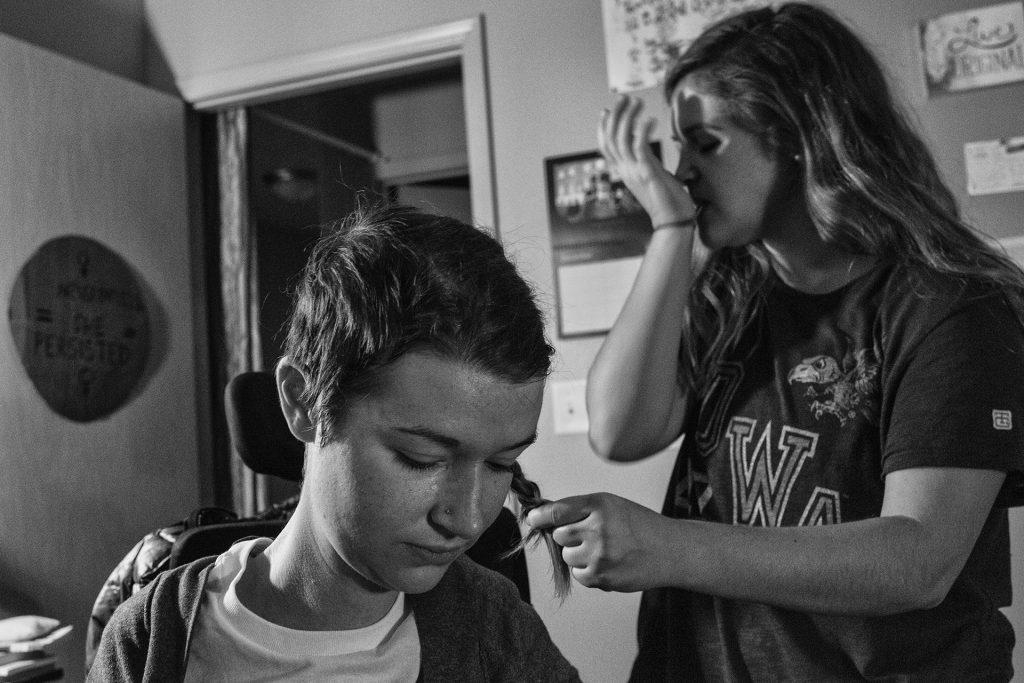 Hannah's helper Claire braids Hannah's hair before she goes to bed in her apartment on Washington St. in Iowa City. (Ben Allan Smith/The Daily Iowan)