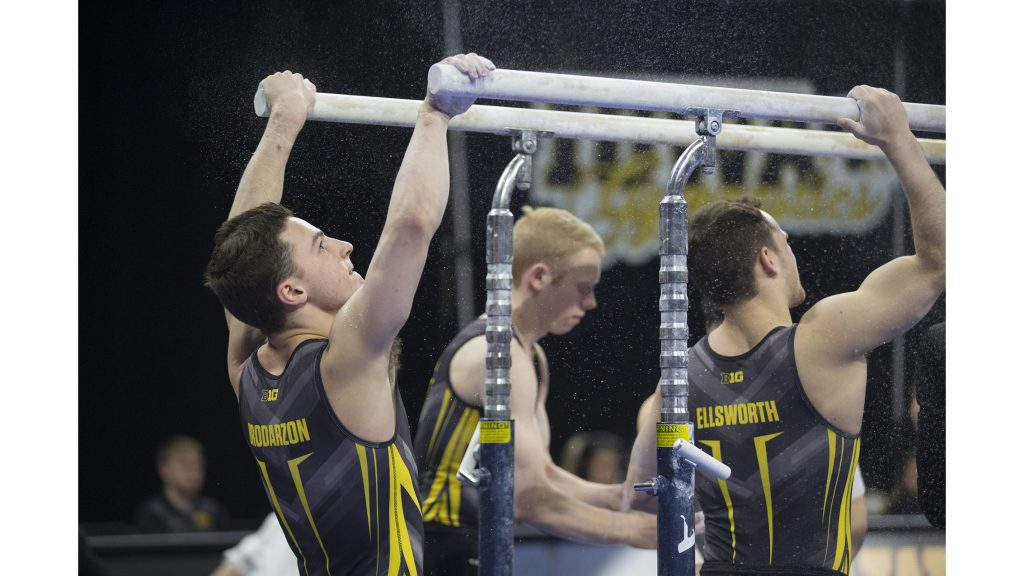 Hawkeye+members+Jake+Brodarzon%2C+Nick+Merryman%2C+and+Dylan+Ellsworth+put+chalk+on+the+parallel+bars+before+they+compete+during+men%27s+gymnastics+Iowa+vs.+Penn+State+and+Arizona+State+on+March+3%2C+2018+at+Carver+Hawkeye+Arena.