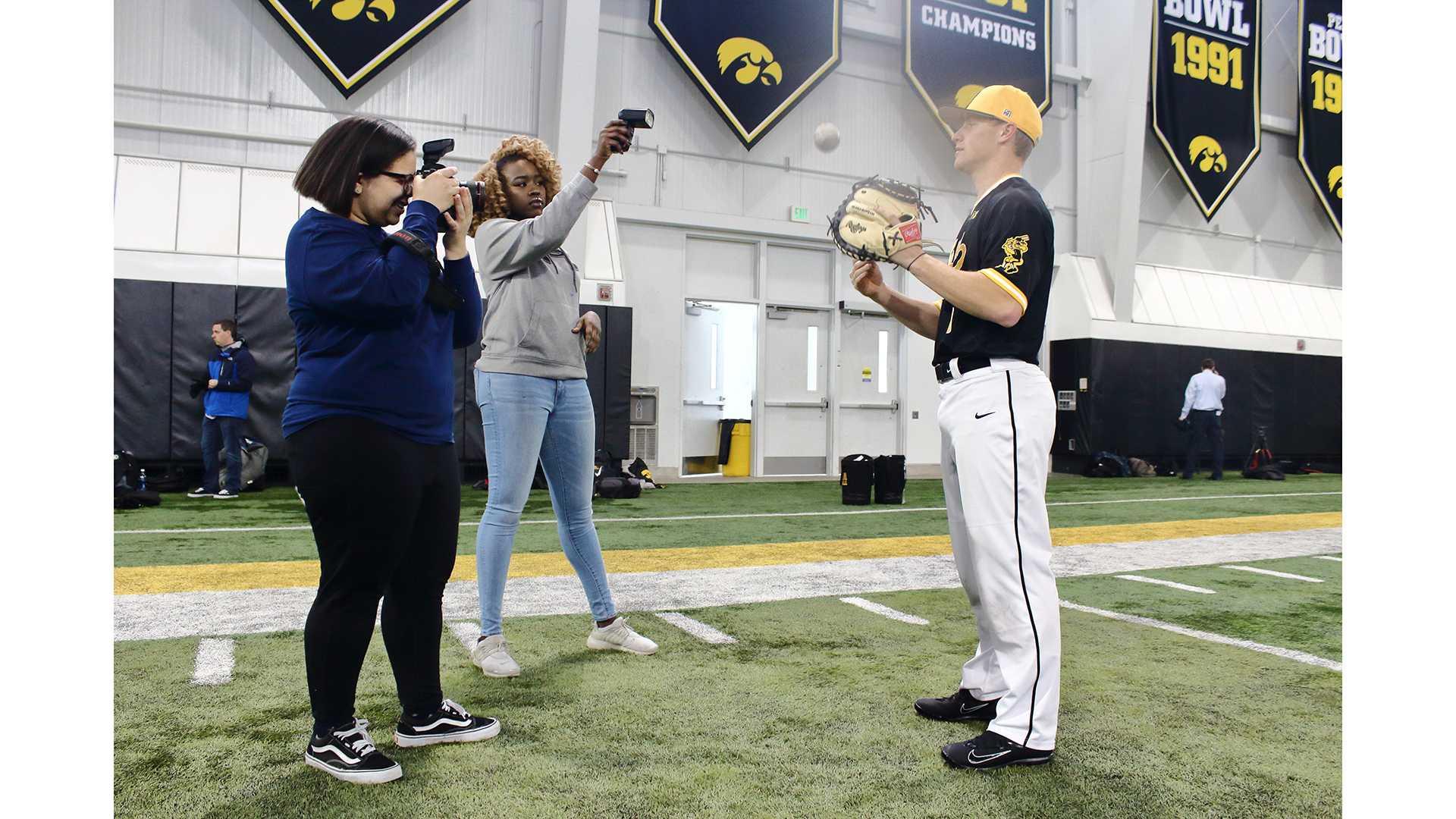 From left: Daily Iowan photo editor Lily Smith and Ashol Aguek photograph Iowa catcher Tyler Cropley at Baseball Media Day on February 8, 2018. (Ashley Morris/The Daily Iowan)
