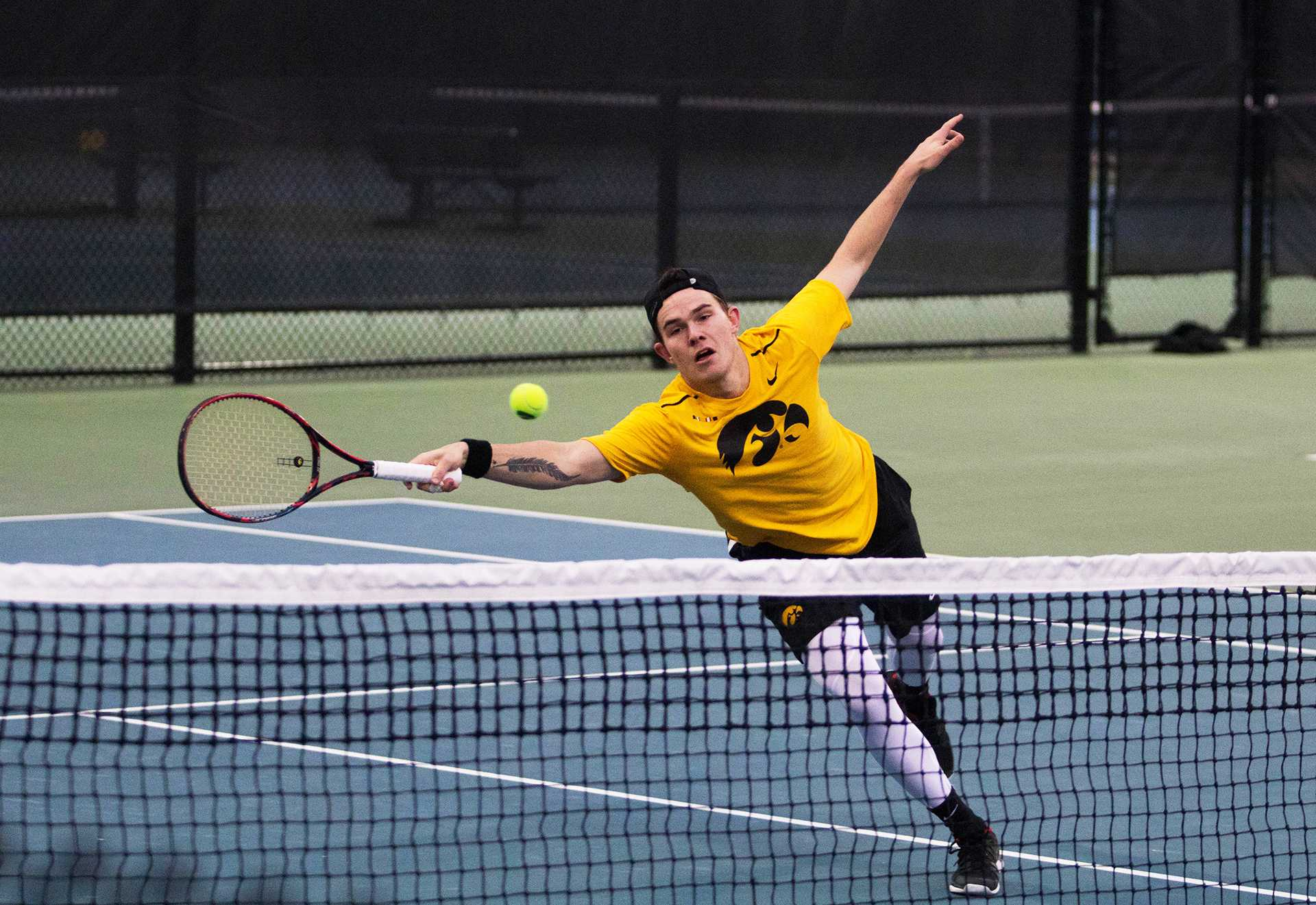 Jonas Larsen reaches for the ball during a match against Indiana at the HTRC on April 13, 2018. The Hawkeyes were defeated 4-3.