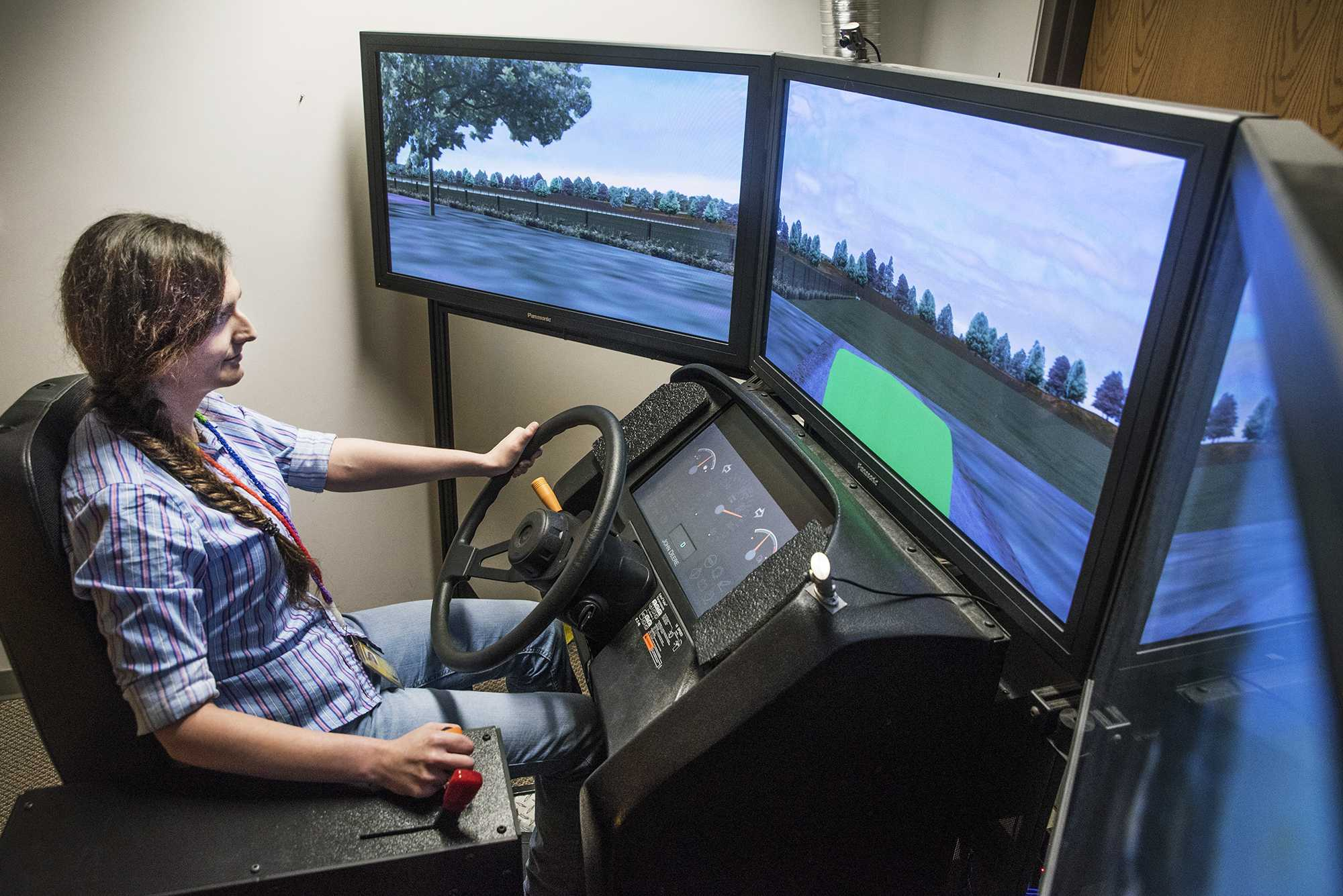 Kayla Faust operates the miniSim, one of only two such driving simulators in the world, at the National Advanced Driving Simulator in Coralville, Iowa. Designed to puts farmers on virtual roads and fields, the miniSim uses steering, pedals, shifters, and a seat from an actual tractor to replicate potentially dangerous driving situations. Faust hopes to find changes that need to be made in farming equipment to avoid accidents. (The Daily Iowan/Olivia Sun)