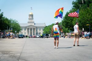Participants in Iowa City Pride parade walk towards the old capital.