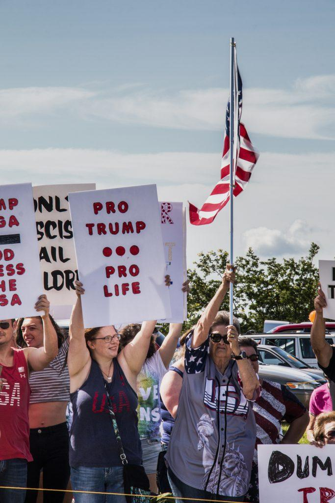 Attendees await the arrival of the president outside of Northeast Iowa Community College in Peosta on July 26, 2018. Both pro- and anti-Trump demonstrators were present at the event. (Katina Zentz/The Daily Iowan)