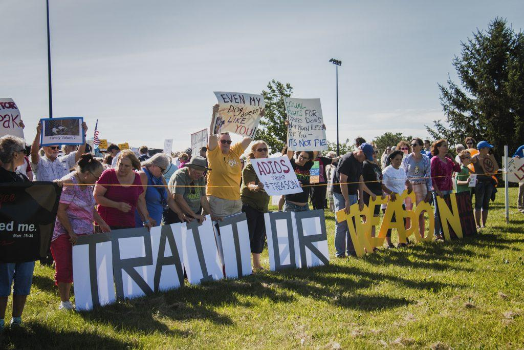 Attendees hold up signs outside of Northeast Iowa Community College in Peosta on July 26, 2018. Both pro- and anti-Trump demonstrators were present for the arrival of the president. (Katina Zentz/The Daily Iowan)