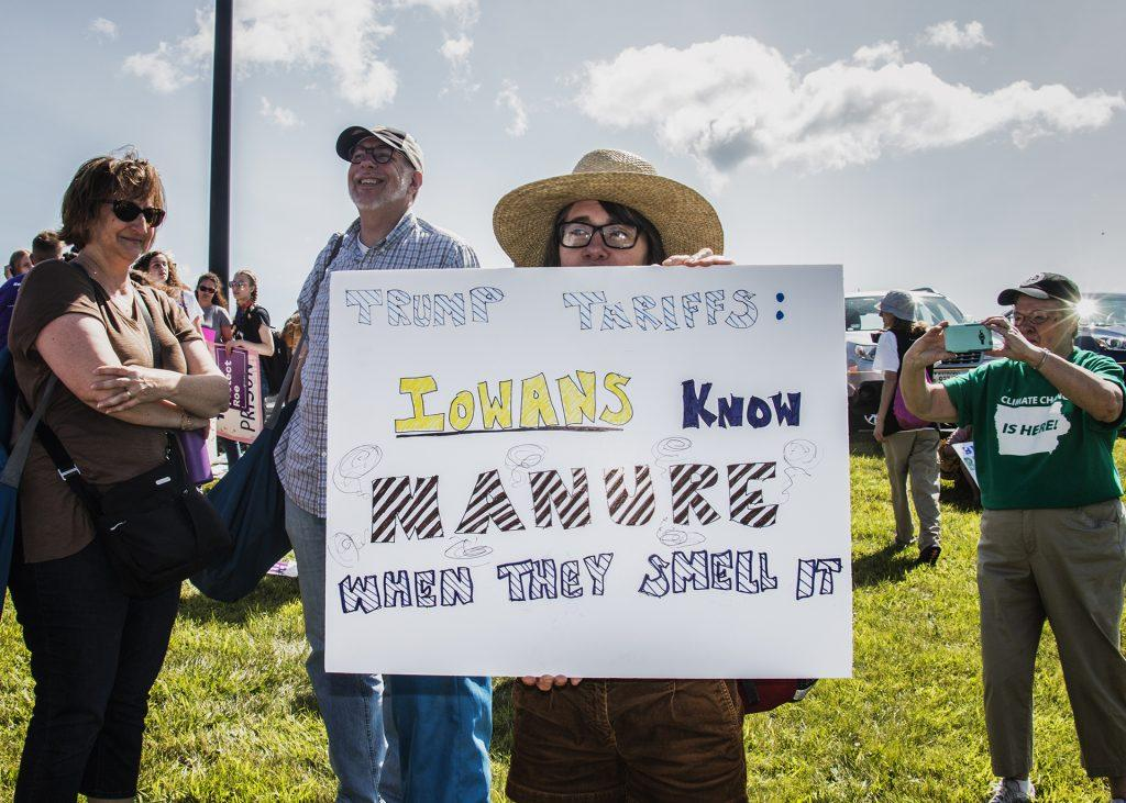 An attendee holds up a sign outside of Northeast Iowa Community College in Peosta on July 26, 2018. Both pro- and anti-Trump demonstrators were present for the arrival of the president. (Katina Zentz/The Daily Iowan)