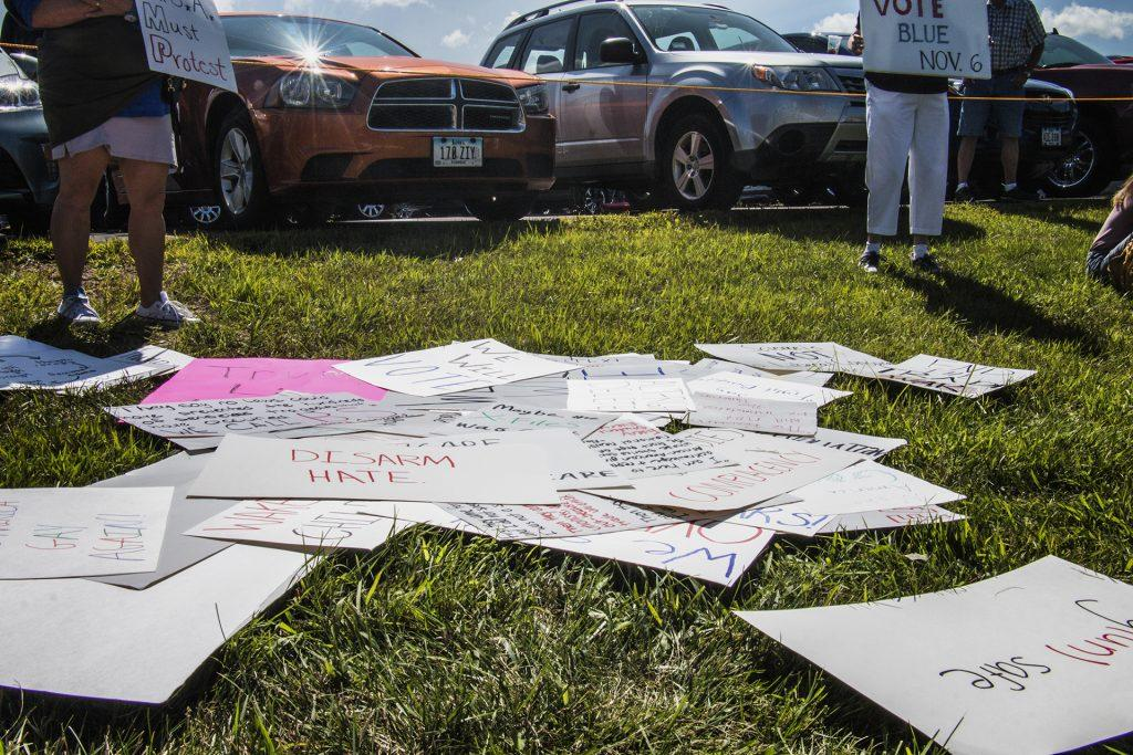 Posters are seen on the ground outside of Northeast Iowa Community College in Peosta on July 26, 2018. Both pro- and anti-Trump demonstrators were present for the arrival of the president. (Katina Zentz/The Daily Iowan)
