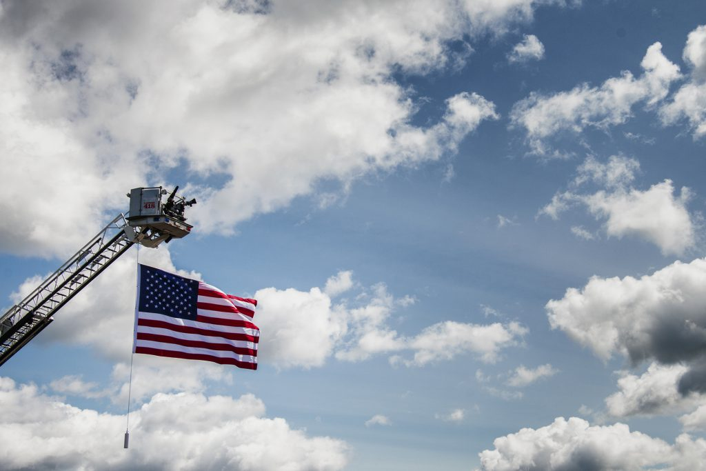 The American flag hangs in the air outside of Northeast Iowa Community College in Peosta on July 26, 2018. Both pro- and anti-Trump demonstrators were present for the arrival of the president. (Katina Zentz/The Daily Iowan)