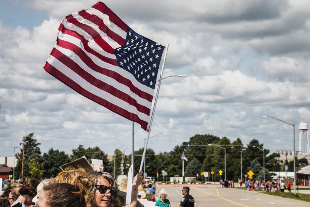 Attendees wave the American flag outside of Northeast Iowa Community College in Peosta on July 26, 2018. Both pro- and anti-Trump demonstrators were present for the arrival of the president. (Katina Zentz/The Daily Iowan)