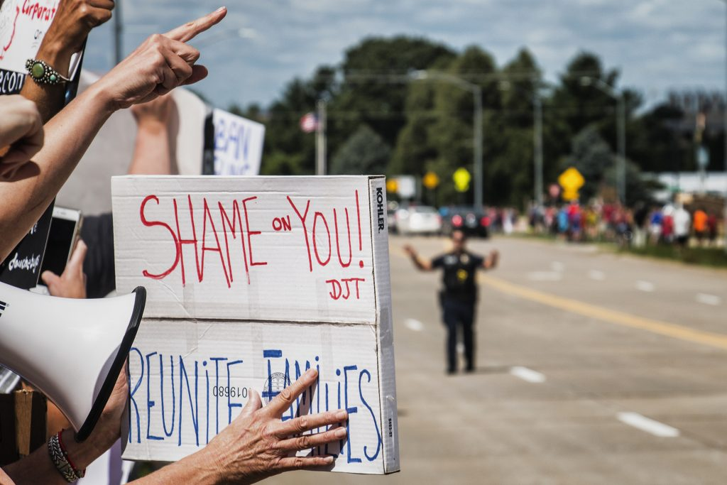 Attendees hold signs outside of Northeast Iowa Community College in Peosta on July 26, 2018. Both pro- and anti-Trump demonstrators were present for the arrival of the president. (Katina Zentz/The Daily Iowan)
