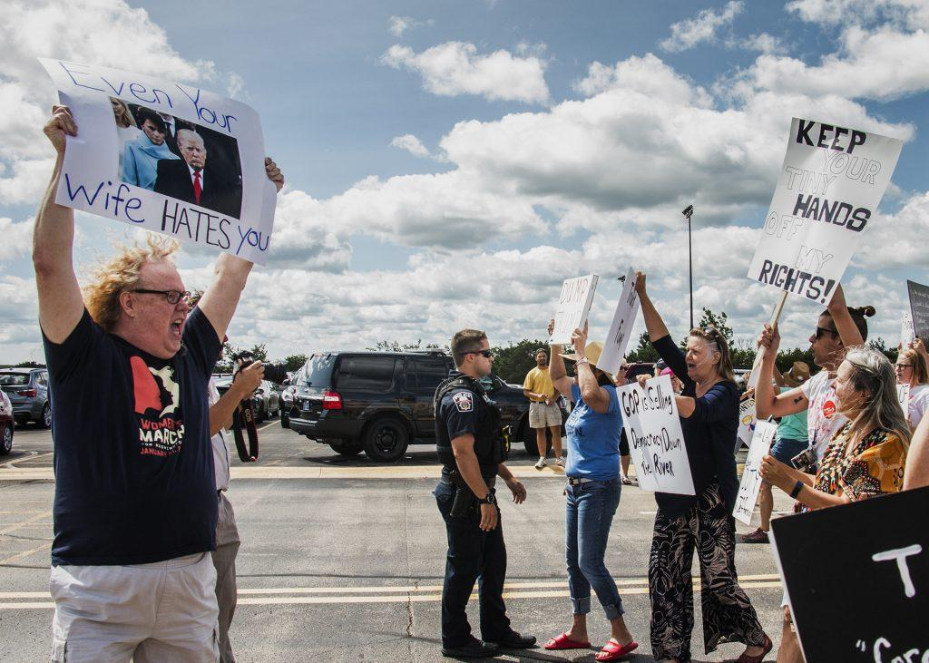 Attendees march toward Northeast Iowa Community College in Peosta on July 26, 2018. Both pro- and anti-Trump demonstrators were present for the arrival of the president. (Katina Zentz/The Daily Iowan)
