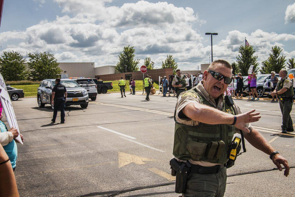 An officer pushes back the crowd outside of Northeast Iowa Community College in Peosta on July 26, 2018. Both pro- and anti-Trump demonstrators were present for the arrival of the president. (Katina Zentz/The Daily Iowan)