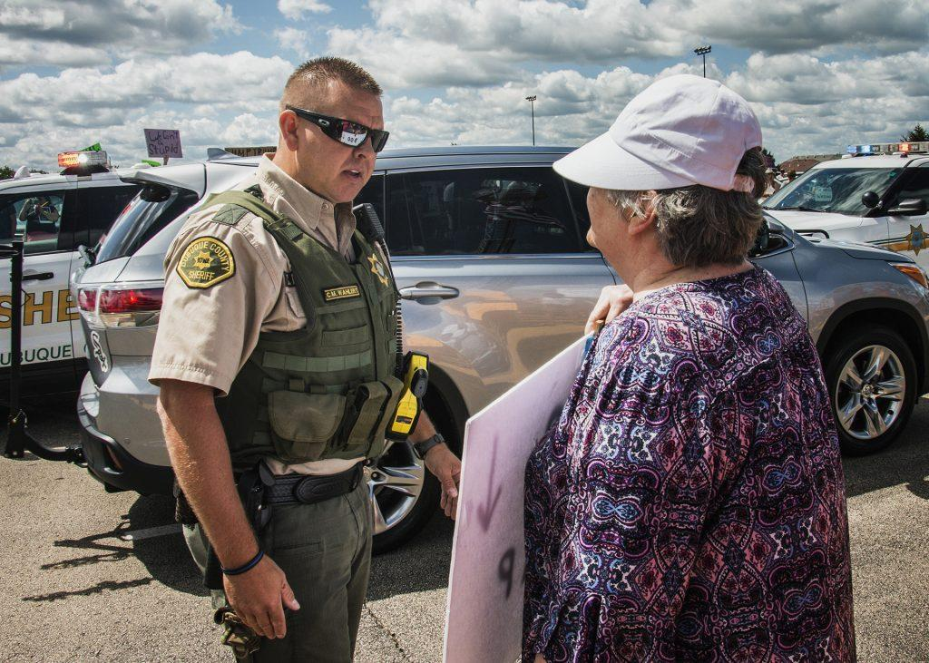 An attendee holds a sign in front of an officer outside of Northeast Iowa Community College in Peosta on July 26, 2018. Both pro- and anti-Trump demonstrators were present for the arrival of the president. (Katina Zentz/The Daily Iowan)