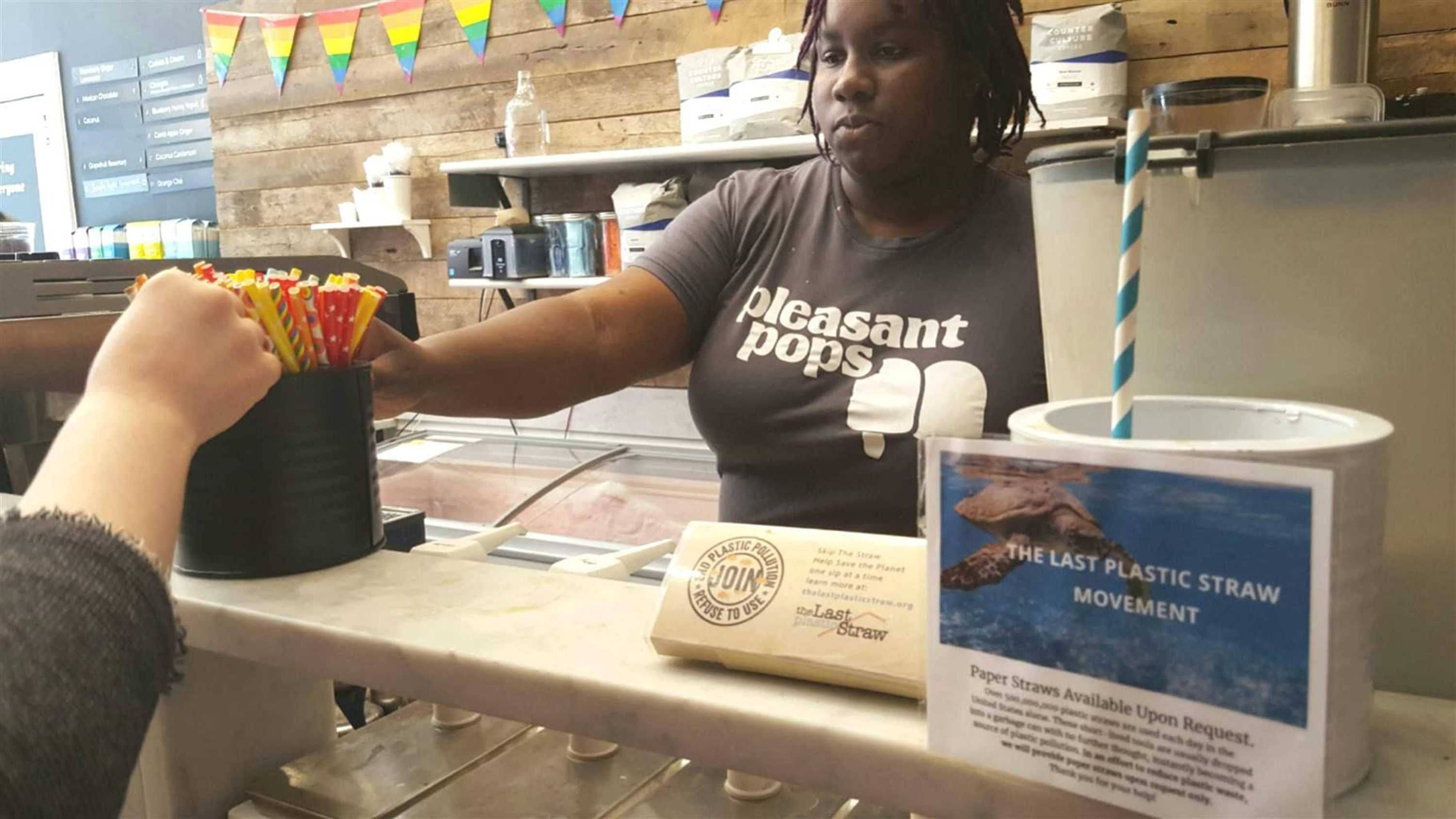 Nadia Bartholomew, a worker at Pleasant Pops coffee and treats shop in Washington, D.C., offers a customer a selection of paper straws. Pleasant Pops has joined the