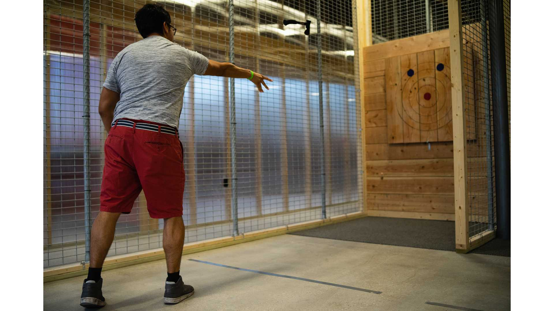 A customer throws a hatchet during the soft opening of Hatchet Jack's on Saturday, June 30, 2018. Hatchet Jack's will be opening soon and allows patrons to throw axes while enjoying beer and wine. (Matthew Finley/The Daily Iowan)
